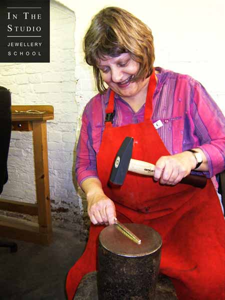 Silver spoon forging with hammer